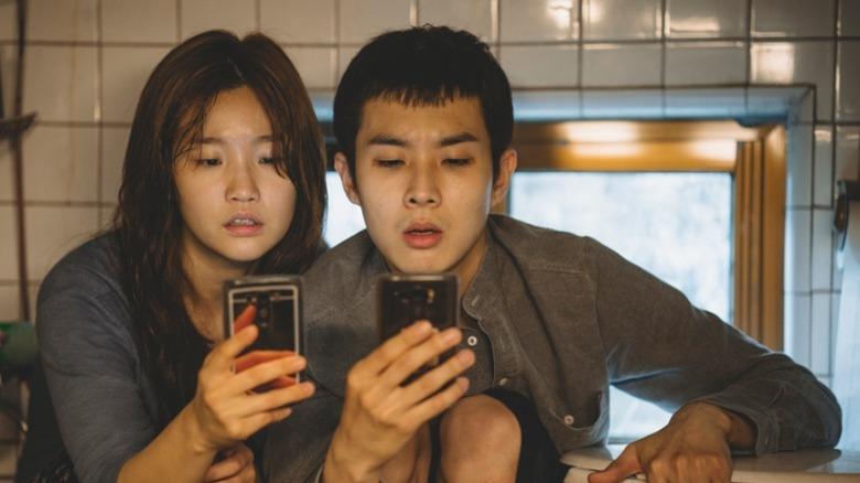 Kim Ki-jung and Kim Ki-woo check phones