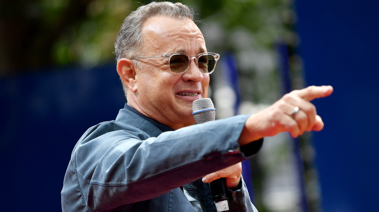 Tom Hanks holding microphone and pointing