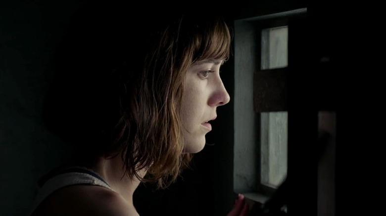 Mary Elizabeth Winstead peers out the bunker window in 10 Cloverfield Lane