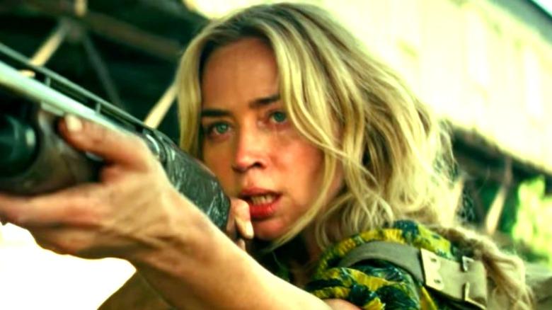 Emily Blunt pointing shotgun
