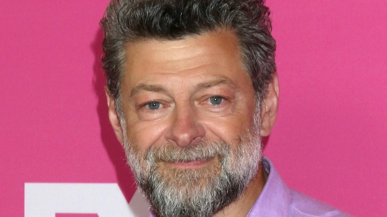 Andy Serkis with gray beard smiling pink background