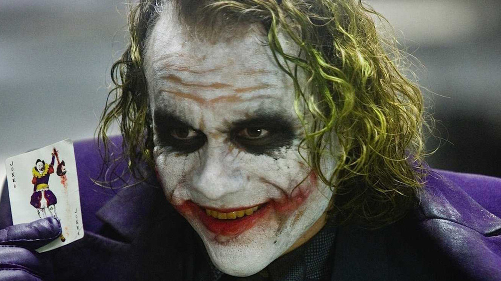 Joker holds up playing card