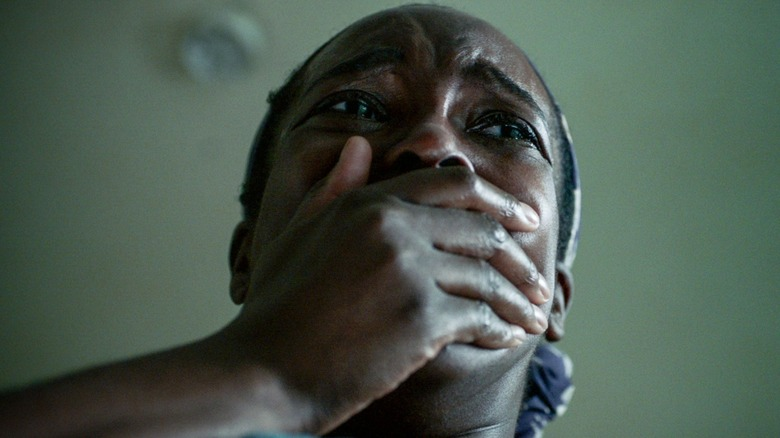 Actor Wunmi Mosaku covering her mouth in a scene from His House