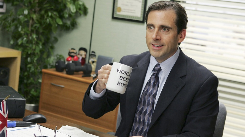 Steve Carell raising a World's Best Boss mug as Michael Scott in The Office
