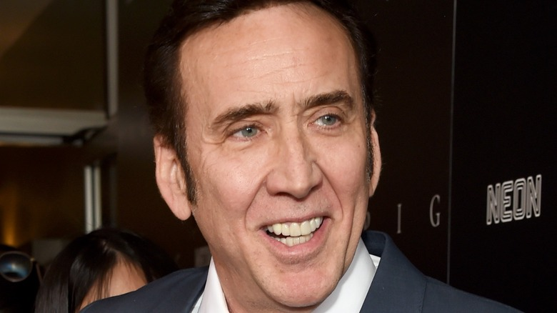 Nicolas Cage smiling and wearing gray suit