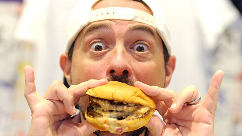Kevin Smith posing with a cheeseburger