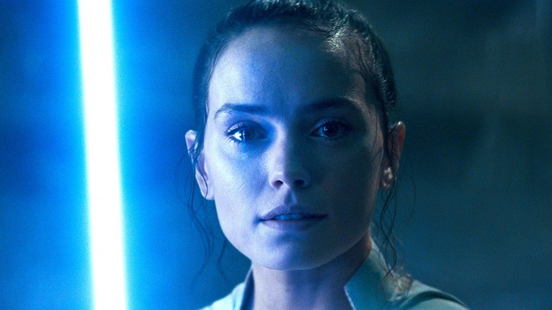 Rey smiling with lightsaber