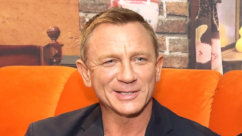 Daniel Craig sitting on orange couch