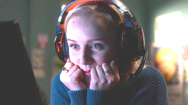 Meg excitedly watching screen smiling wearing headphones
