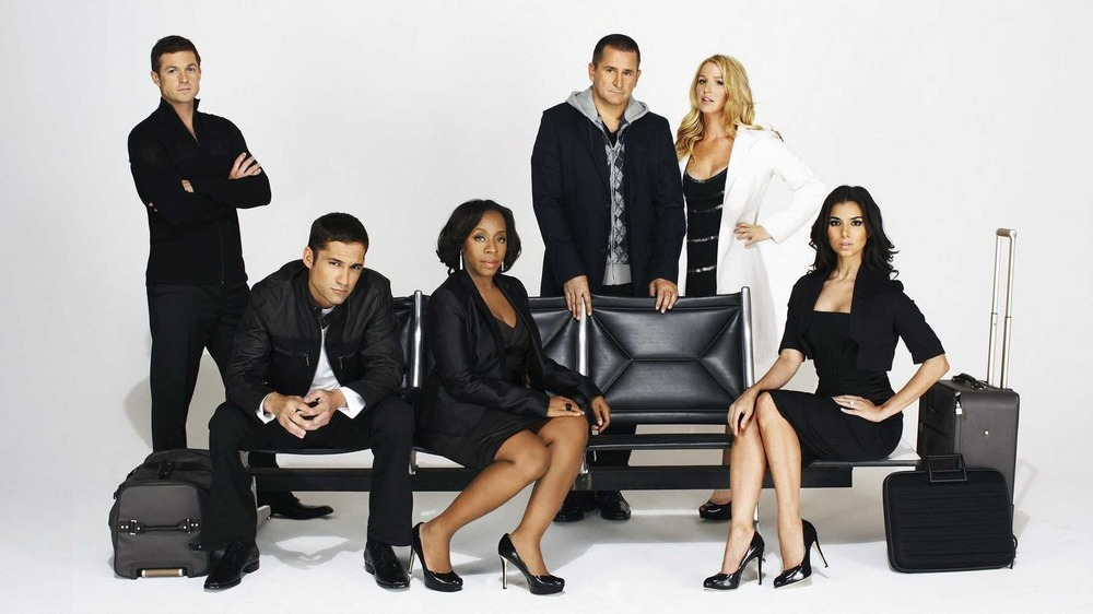 The cast of Without a Trace sitting on airplane seating in a promotional still
