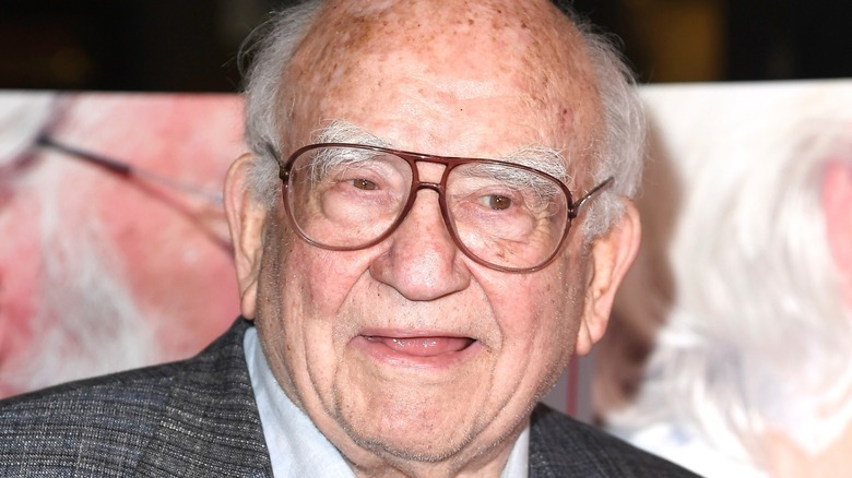 Ed Asner wearing glasses and smiling