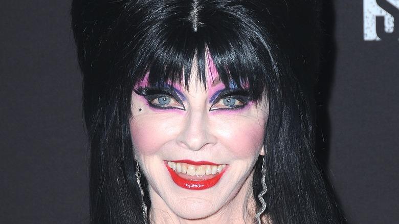 Elvira in wig and purple eye makeup smiling