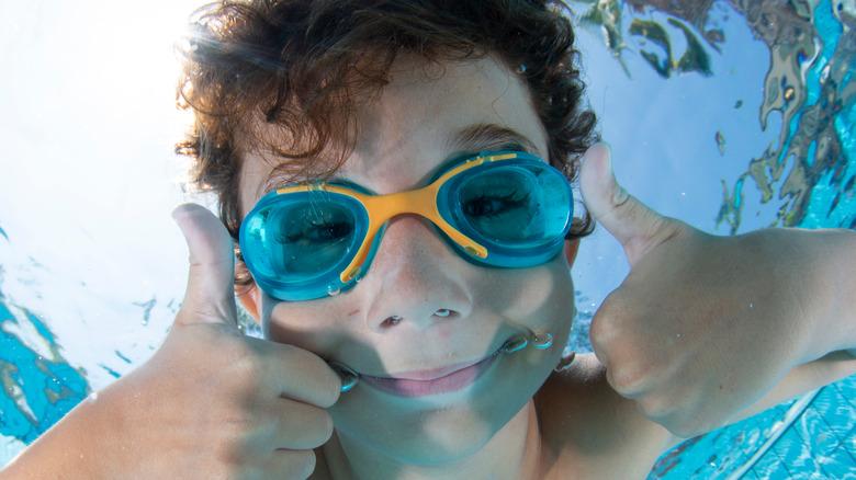Kid wearing goggles swimming