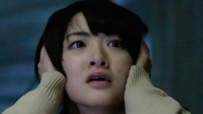 Japanese schoolgirl covering ears