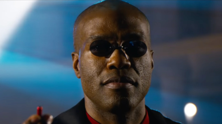 Morpheus holding red pill The Matrix Resurrections