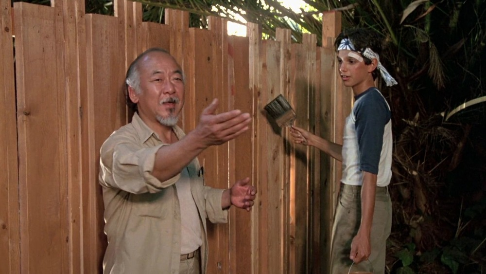 Mr. Miyagi and Daniel paint a fence in The Karate Kid