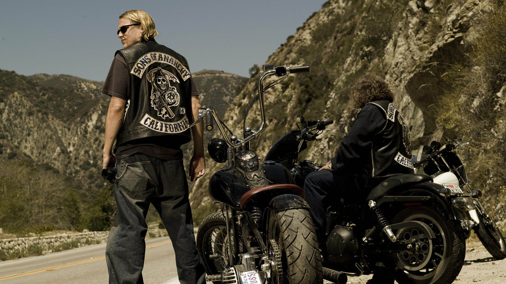 Charlie Hunnam standing next to a motorcycle on Sons of Anarchy