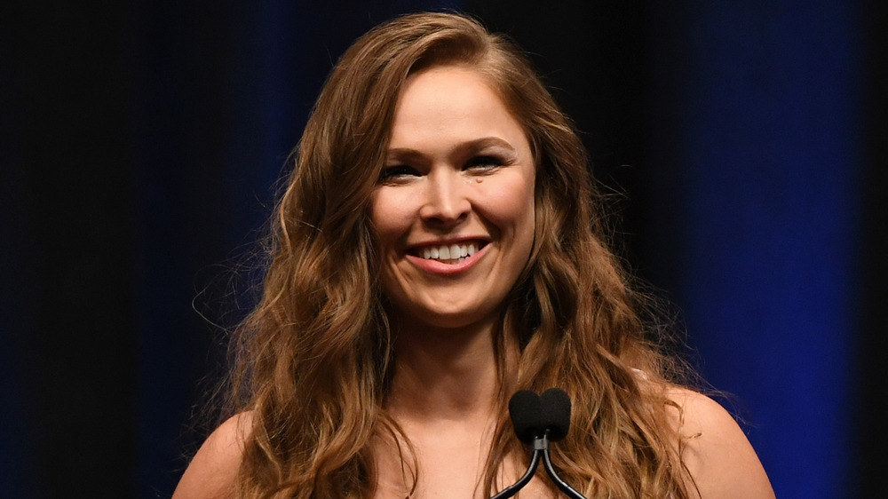 Ronda Rousey smiling in front of microphone