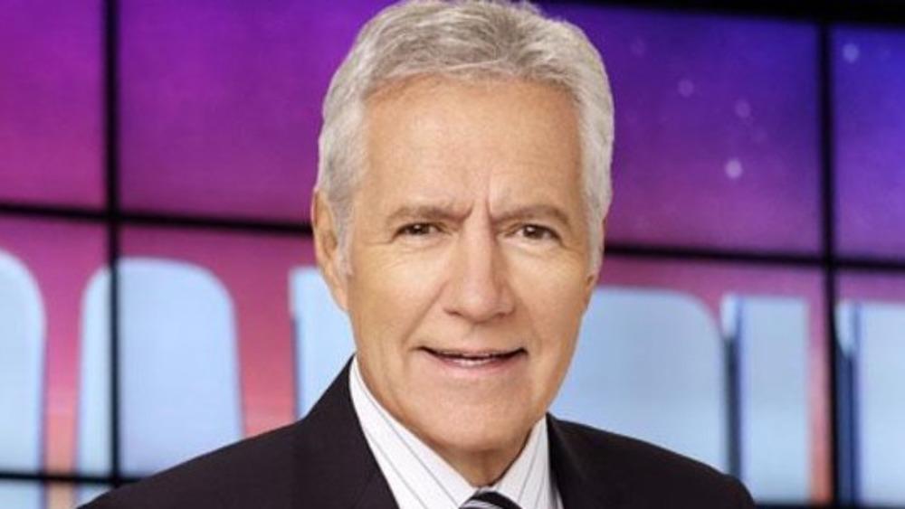 Alex Trebek stands on the Jeopardy set