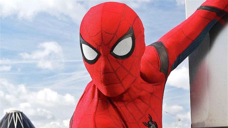Spider-Man holding onto skyscraper