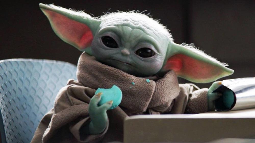Baby Yoda, also known as Grogu, eats blue macarons on The Mandalorian