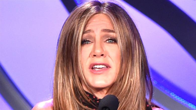 Jennifer Aniston holds a microphone