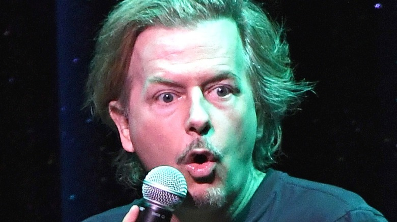 David Spade performing with microphone