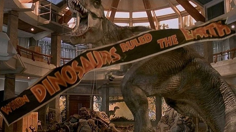 """A Tyrannosaurus Rex roars inside a building while a banner reading """"when dinosaurs walked the Earth"""" falls"""