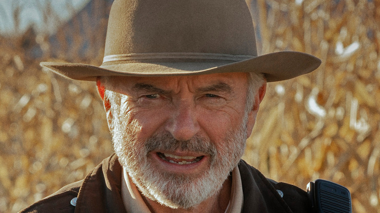 Sam Neill squinting and wearing hat