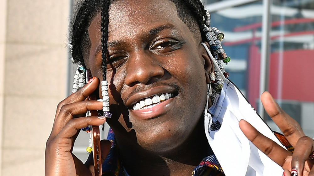 Lil Yachty talks on a cell phone and gives a peace sign