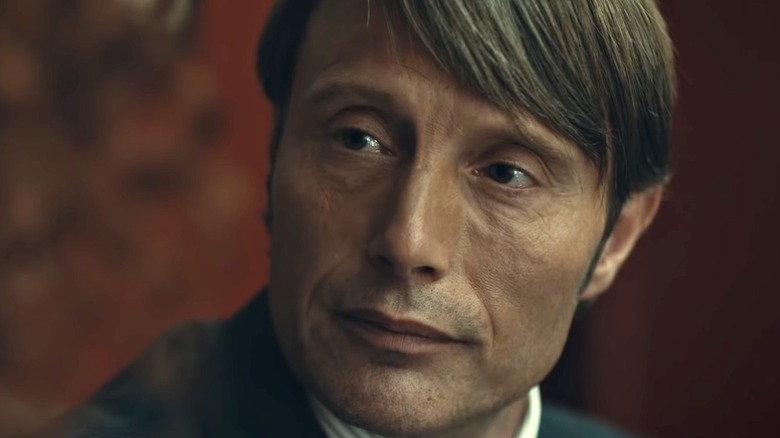 Mads Mikkelsen as Hannibal in front of red wall