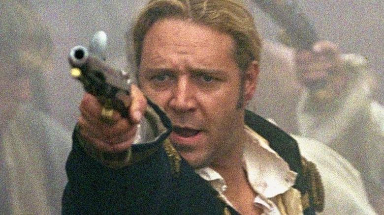 Captain Jack Aubrey pointing a gun