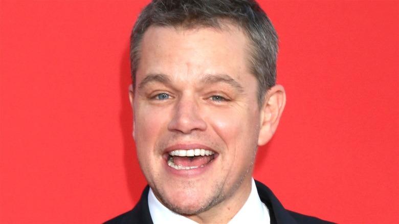 Matt Damon smiling red background