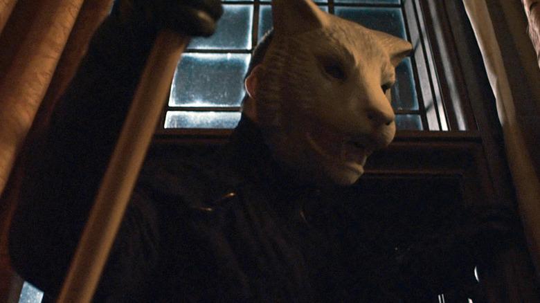 masked killer climbing into window