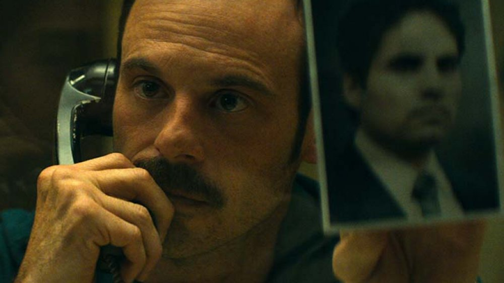 Scoot McNairy as Walt Breslin holding up a picture of Kiki Camarena (Michael Peña) in 'Narcos: Mexico' season 2