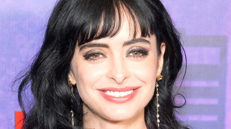 Krysten Ritter smiling with purple background