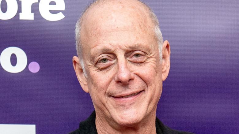 Mark Blum against purple backdrop smiling