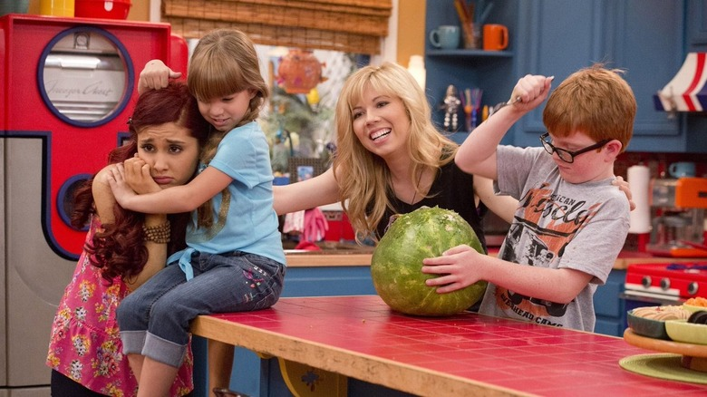 Sam, Cat, and kids carving a watermelon