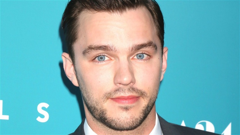 Nicholas Hoult smiling with teal background