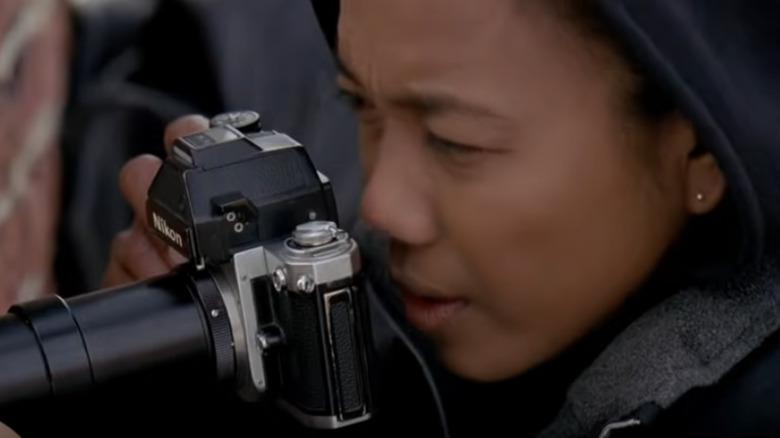 Kima Greggs looks through camera
