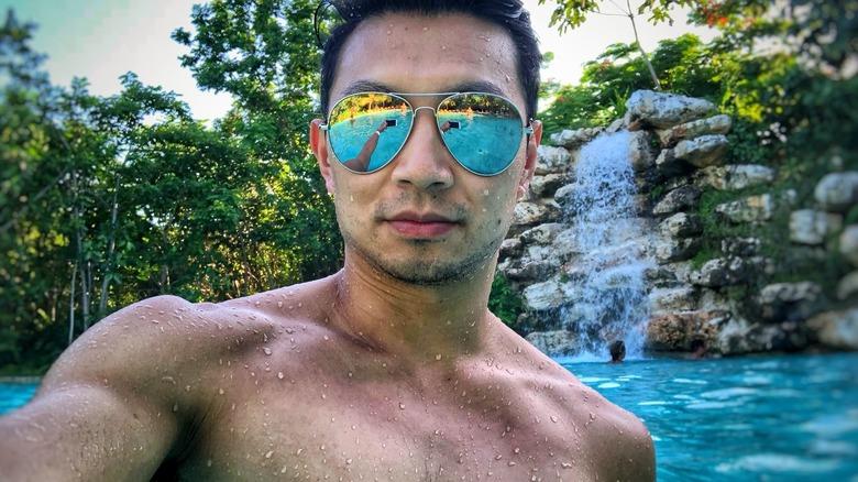 Simu Liu taking a shirtless selfie with sunglasses in a pool