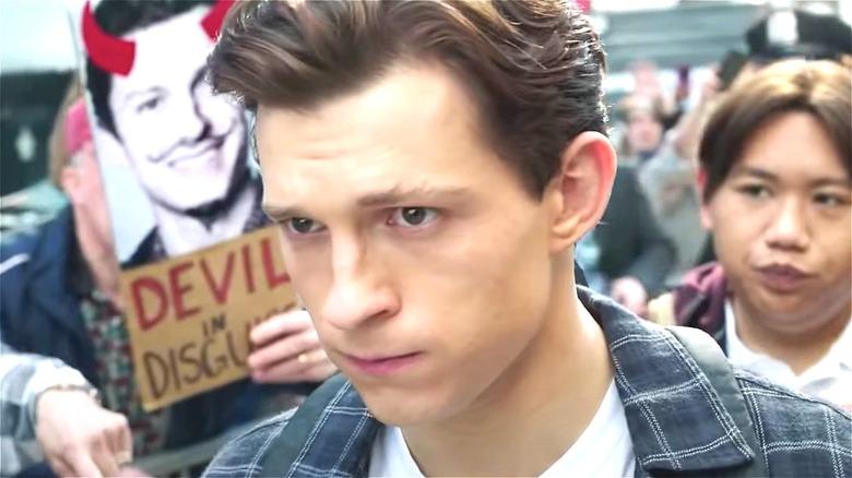 Peter Parker walking past devil poster