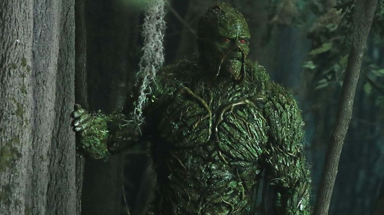 Swamp Thing peers off into the distance while touching a tree