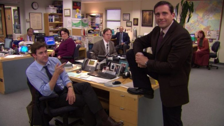 The Office cast, Steve Carell standing with his foot on Jim's desk