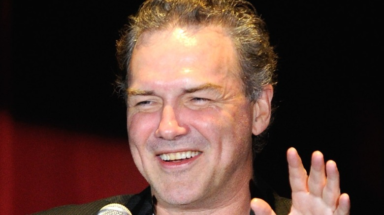 Norm Macdonald laughing and holding hand up