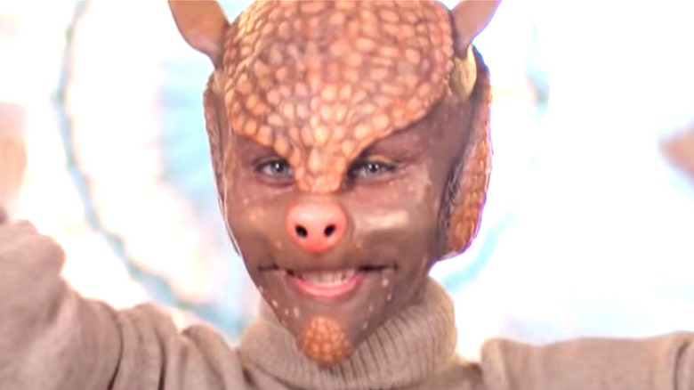 Person wearing prosthetic armadillo mask