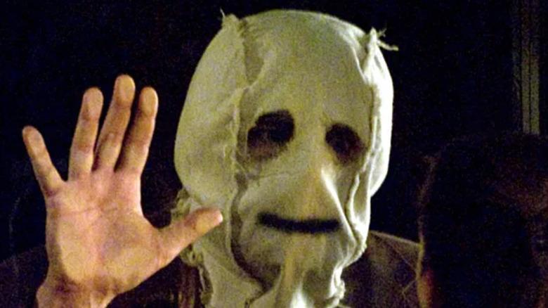 masked man staring window