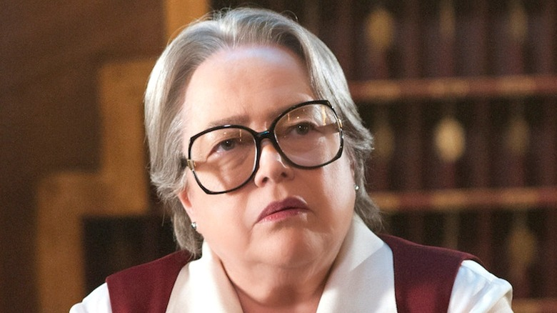 Kathy Bates in glasses behind the check-in desk at Hotel Cortez