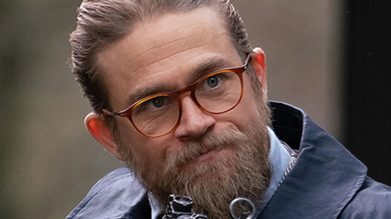 Charlie Hunnam wearing glasses and holding gun