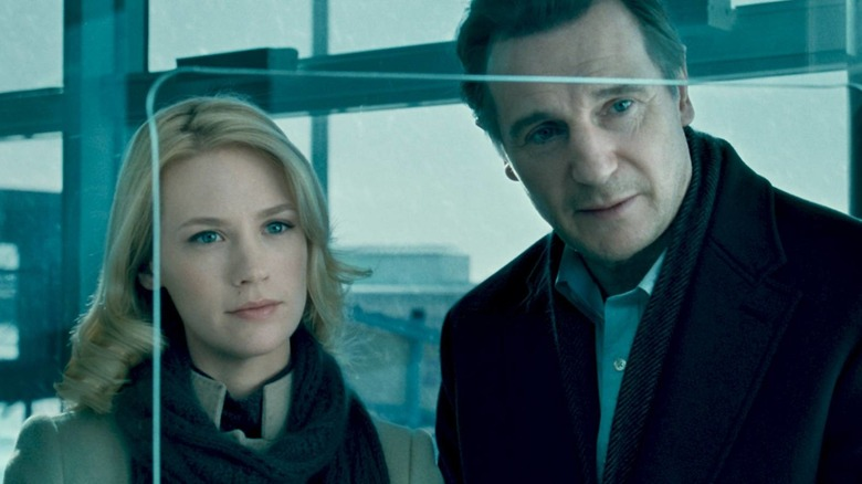 Liam Neeson and Diane Kruger look across a ticket counter